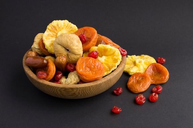 Diferentes frutas secas no laço marrom no fundo preto