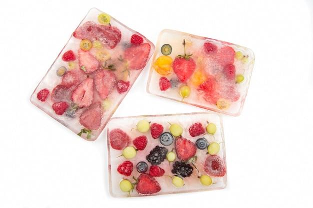 Diferentes frutas suculentas congeladas no gelo