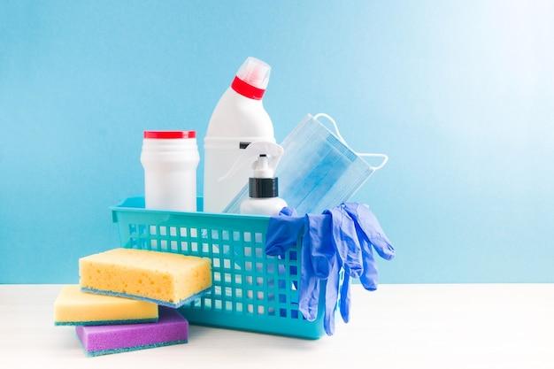 Diferentes garrafas de plástico com produtos de limpeza, luvas descartáveis de borracha e uma máscara protetora de tecido em uma cesta de plástico azul