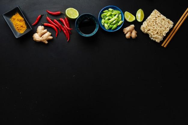 Diferentes ingredientes de comida asiática em superfície escura