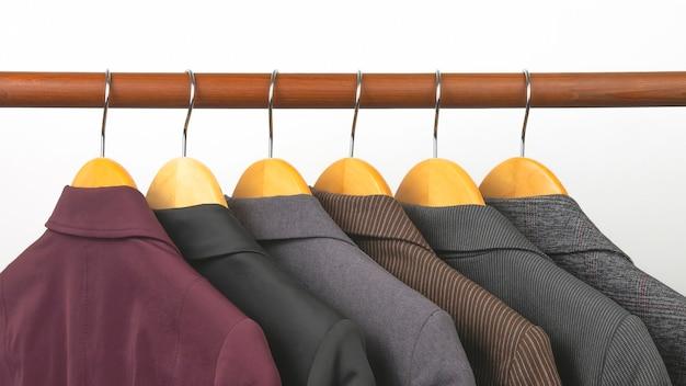 Diferentes jaquetas femininas clássicas de escritório penduradas em um cabide para guardar roupas