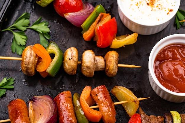 Diferentes kebabs grelhados com carne, cogumelos, salsichas e vegetais no espeto