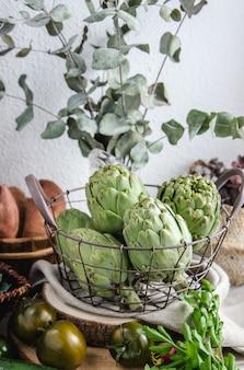 Diferentes legumes e alcachofras sazonais em uma cesta de metal
