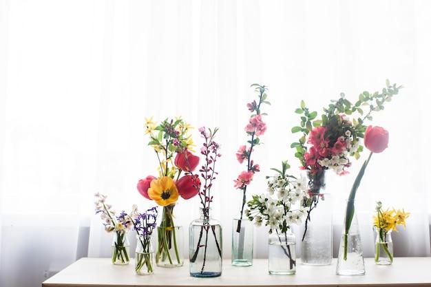Diferentes lindas flores em potes com água na mesa perto da janela