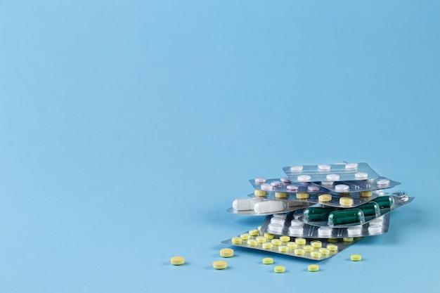 Diferentes medicamentos em comprimidos e cápsulas em fundo azul.