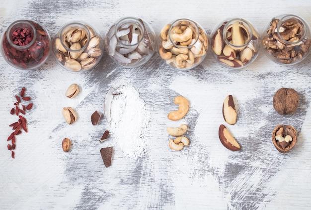 Diferentes nozes em potes pequenos sobre um fundo claro de madeira, um conceito de alimentação saudável