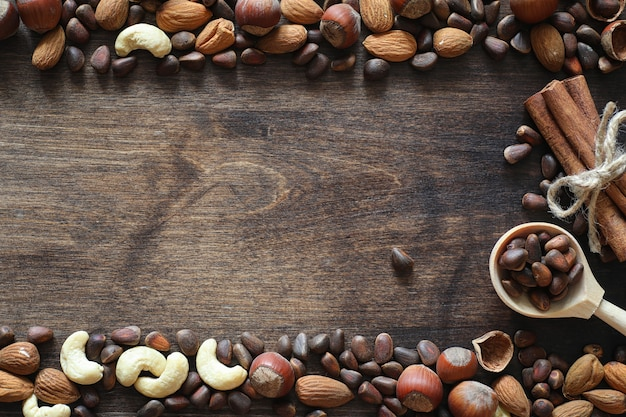 Diferentes nozes em uma mesa de madeira. cedro, caju, avelã, nozes e uma colher na mesa. muitas nozes são inshell e chistchenyh em um fundo de madeira