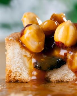 Diferentes nozes em uma tartelete redonda, uma tartelete redonda com nozes e frutas secas com caramelo
