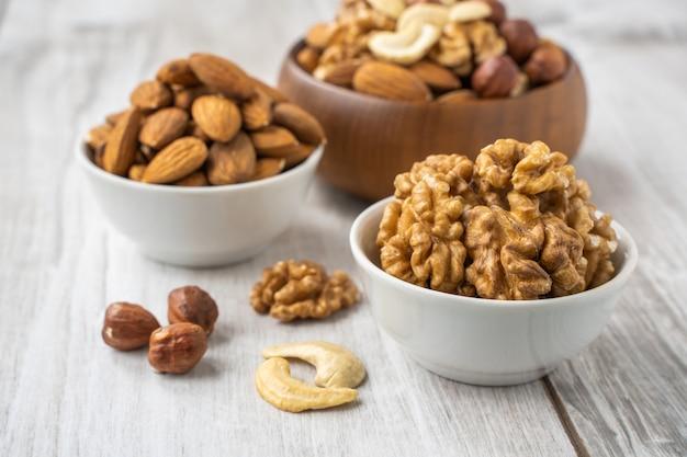 Diferentes nozes nas tigelas brancas e de madeira na mesa de madeira lignt. sementes de amêndoa, nozes, avelãs e castanhas de caju.