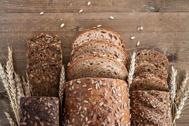Diferentes pães integrais da padaria são cortados em pedaços. composição com sementes, sementes de gergelim e espigas de trigo. vista do topo.
