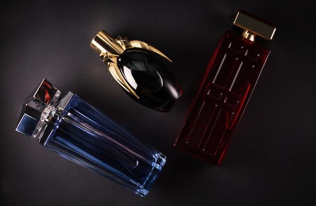 Diferentes perfumes femininos em uma superfície escura