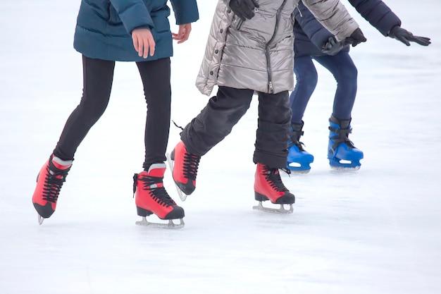 Diferentes pessoas estão patinando ativamente na pista de gelo. hobbies e esportes.