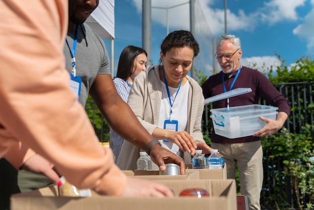 Diferentes pessoas fazendo trabalho voluntário com alimentos