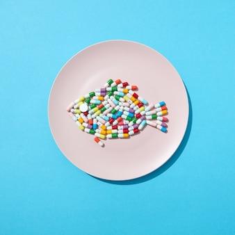 Diferentes pílulas e suplementos como alimentos no prato redondo branco em forma de peixe em uma parede azul. pílulas dietéticas e suplementos para o conceito de dieta. postura plana