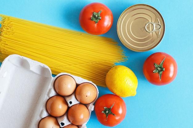 Diferentes produtos alimentares saudáveis em um fundo azul. vista do topo. postura plana. fruta, vegetais, ovos e mercearia online loja
