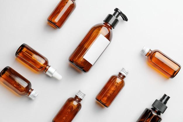 Diferentes produtos cosméticos em frascos em fundo branco