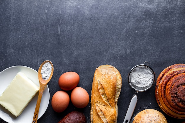 Diferentes produtos de panificação frescos e crocantes e ingredientes de panificação no fundo preto lousa. copie o espaço para receita e texto