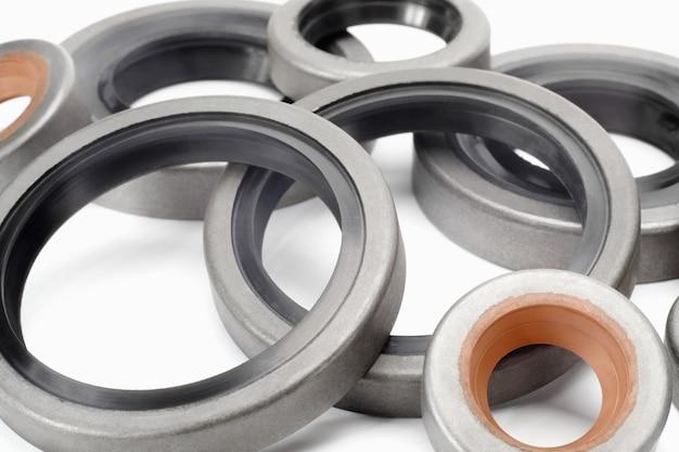 Diferentes retentores de óleo reforçados com borracha para eixos e motores de automóveis em fundo branco, close-up. punhos para evitar vazamento de líquido. peças do carro.