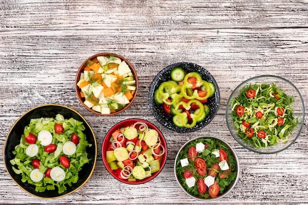 Diferentes saladas de legumes em taças na mesa de madeira