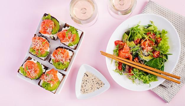 Diferentes saladas saudáveis e sanduíches de salmão