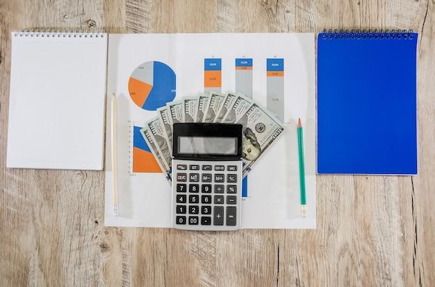 Diferentes tabelas, gráficos com dólares e uma calculadora na mesa do escritório análise financeira