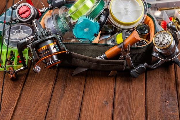 Diferentes táculos de pesca com iscas e molinetes em fundo marrom de madeira com lugar para texto. design para publicidade e publicação.