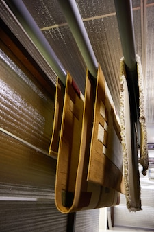 Diferentes tapetes pendurados em prateleiras. limpeza e secagem profissional de carpetes