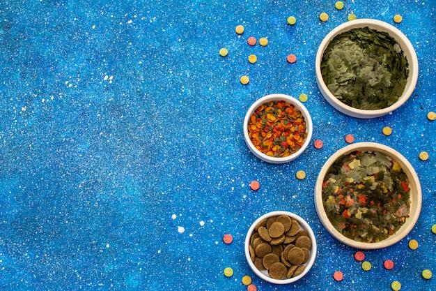 Diferentes tipos de alimentos para peixes de aquário. flocos, spirulina, pílulas, mistura. fundo do mar azul marinho