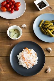 Diferentes tipos de aperitivos, chucrute e pepinos em conserva e tomates em pratos planos de madeira