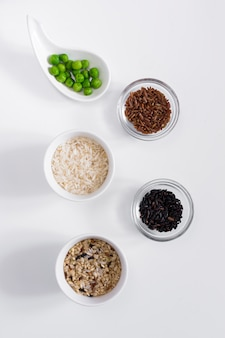 Diferentes tipos de arroz com feijão verde em taças na mesa