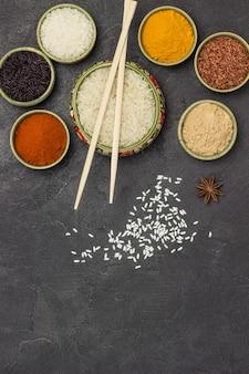 Diferentes tipos de arroz e especiarias secas em tigelas. varas de bambu. postura plana.