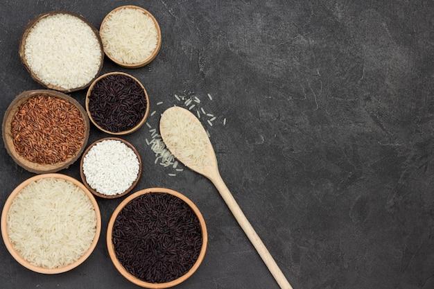 Diferentes tipos de arroz em tigela de cerâmica. arroz branco em uma colher de pau. postura plana