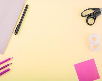 Diferentes tipos de artigos de papelaria em fundo amarelo