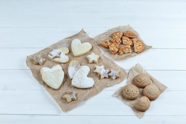 Diferentes tipos de biscoitos em pedaços de sacos em um fundo branco de placa de madeira. colocação plana.