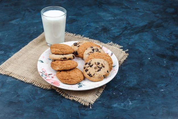 Diferentes tipos de biscoitos, leite em um jogo americano sobre um fundo azul escuro. vista de alto ângulo.