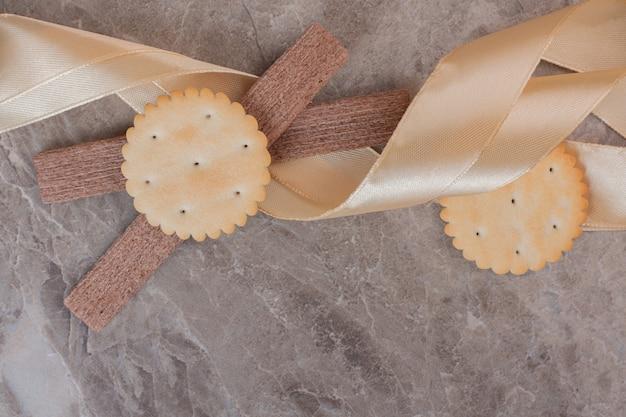 Diferentes tipos de biscoitos na superfície de mármore com fita.