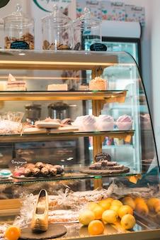 Diferentes tipos de bolos e doces em vitrine de pastelaria