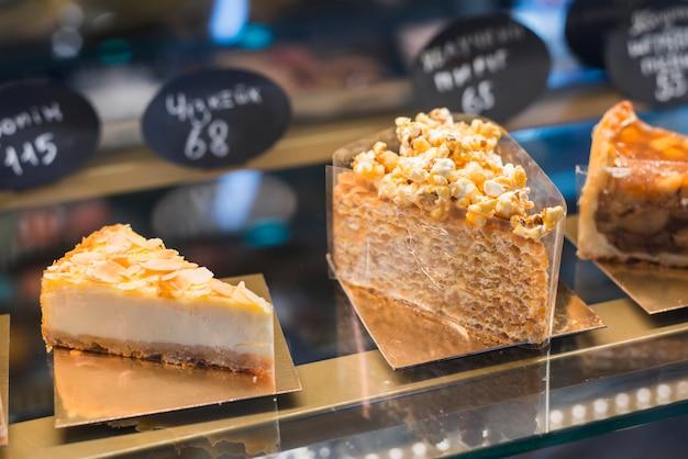 Diferentes tipos de bolos no armário de vidro com etiqueta de preço