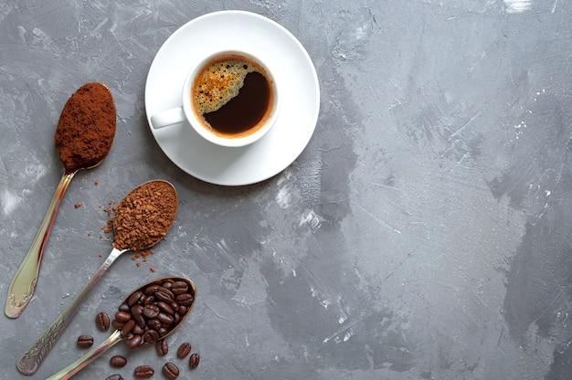 Diferentes tipos de café. café em grão, café moído e solúvel nas colheres e uma xícara de expresso fresco. vista superior, copie o espaço. Foto Premium