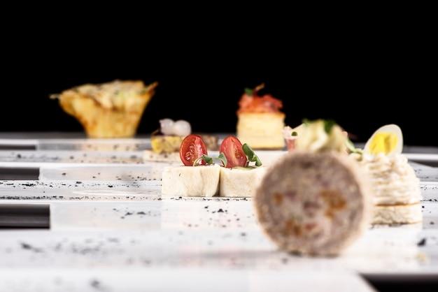 Diferentes tipos de canapés, colocados em pratos individuais, finger food, fundo escuro