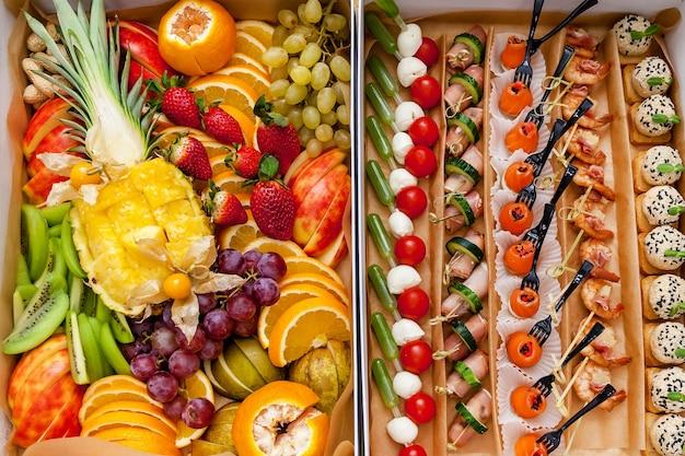 Diferentes tipos de canapés com peixes, verduras frescas e queijos em uma caixa especial sob encomenda. muitas frutas fatiadas como abacaxi, laranja, maçã, kiwi, morango.
