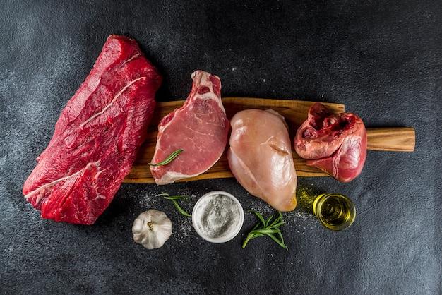 Diferentes tipos de carne com ervas e óleo