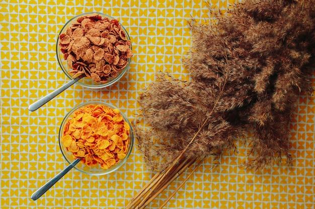 Diferentes tipos de cereais com colher na placa de vidro. nutrição saudável, comida saudável na mesa com flores secas. dois pratos com cereais diferentes.