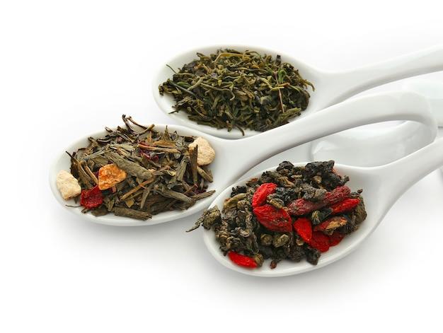 Diferentes tipos de chá seco em colheres de cerâmica, isolado no branco