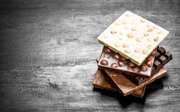 Diferentes tipos de chocolate em barra. no quadro negro.