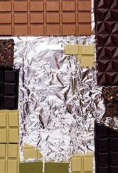 Diferentes tipos de chocolate em uma embalagem de alumínio. copie o espaço. vista de cima. moldura doce