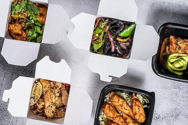 Diferentes tipos de comida asiática em caixas de papel