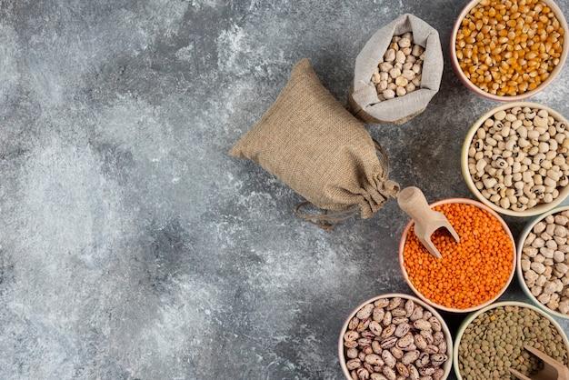Diferentes tipos de composição crua de leguminosas secas na superfície da mesa de mármore.