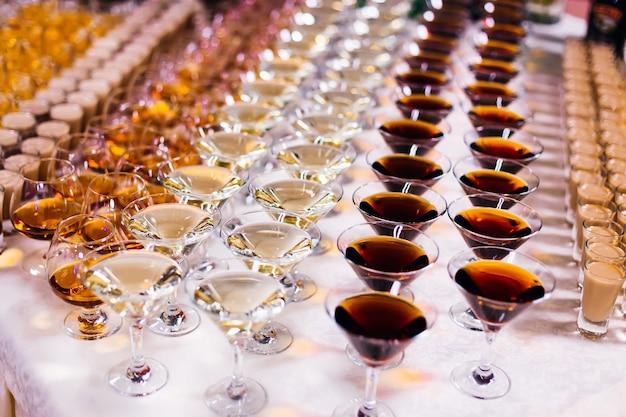 Diferentes tipos de copos e bebidas alcoólicas na mesa de banquete de casamento
