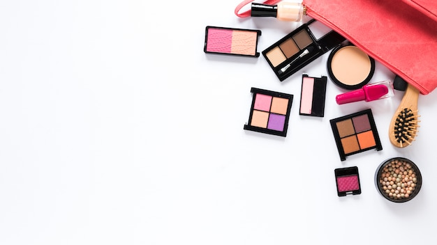 Diferentes tipos de cosméticos espalhados na mesa branca
